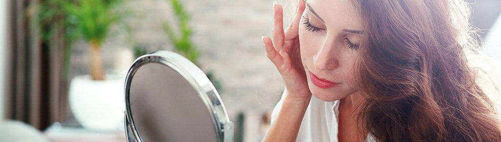 Девушка перед зеркалом для макияжа